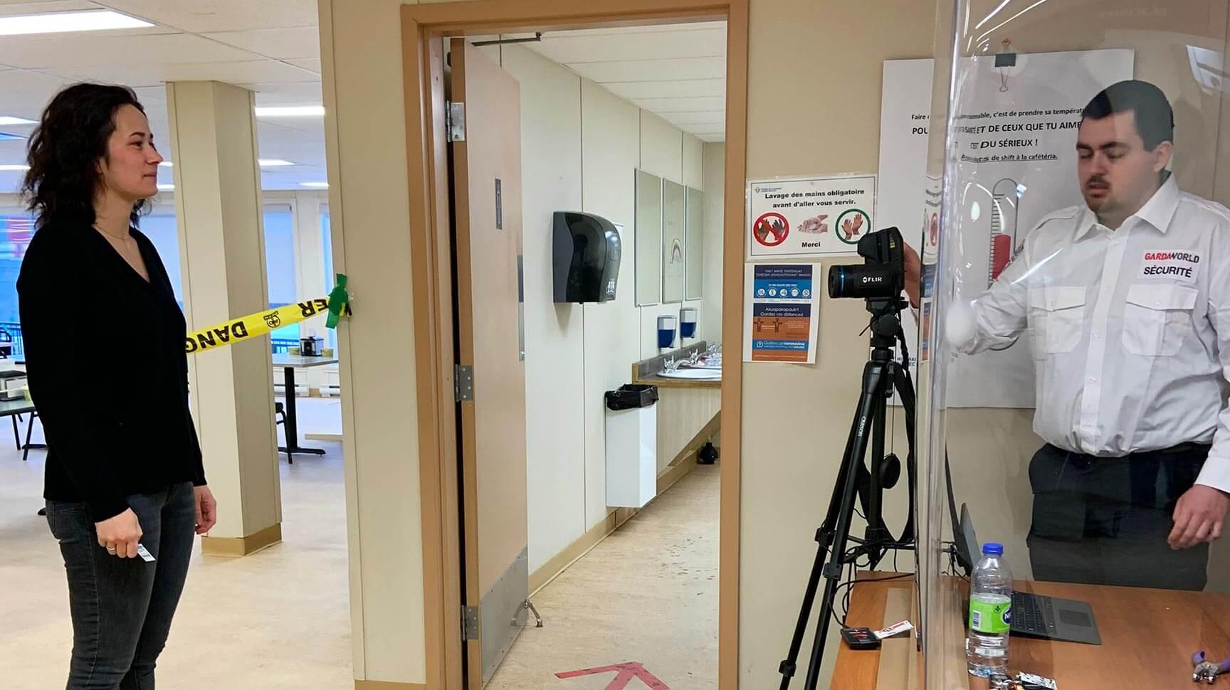 Utilisation d'une caméra thermique pour prendre la température desemployés.
